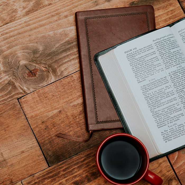 Bible and coffee cup on table