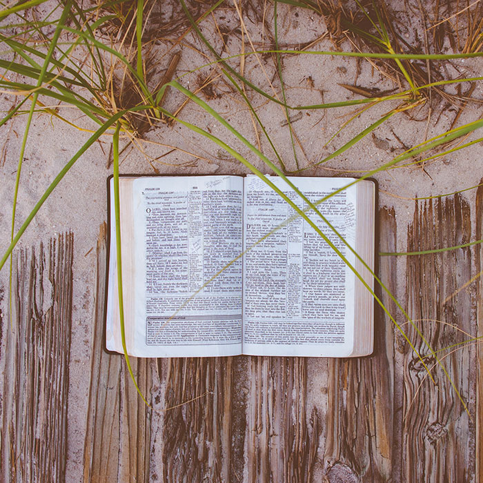 open bible on sandy path