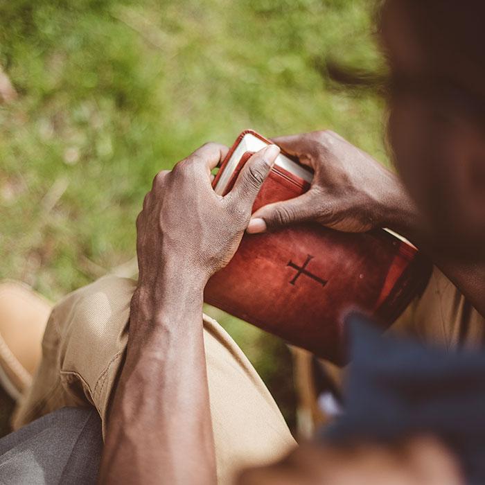 Man holding Bible while praying