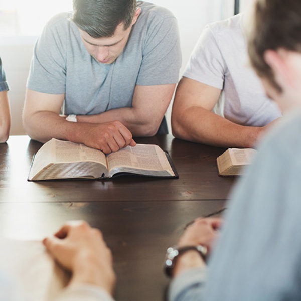 group of men sitting at a table, reading Bibles