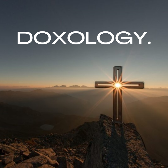 cross on a mountaintop, sun shining behind