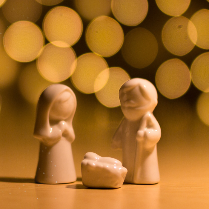 small figurines of Mary, Joseph, Baby Jesus with background of gold lights